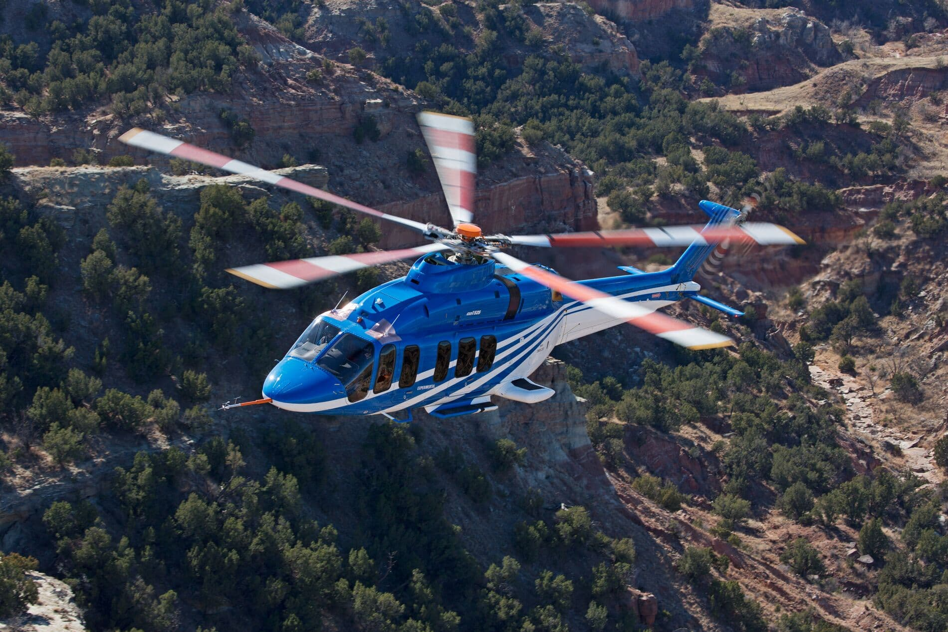 Bell 525 In Flight Over Green Desert Mountains